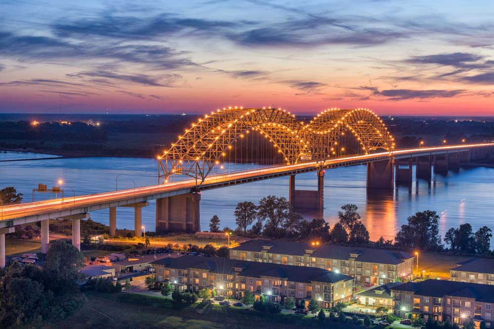 Image of the Hernando de Soto Bridge lit up with lights at sunset.  CrestCore provides real estate and property management services in the Memphis Area.